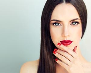 Mooi vrouwelijk model met rode nagels en lippen en bruin lang haar.