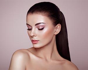 Mooi vrouwelijk model met mooie make-up en bruin lang haar in een staart..