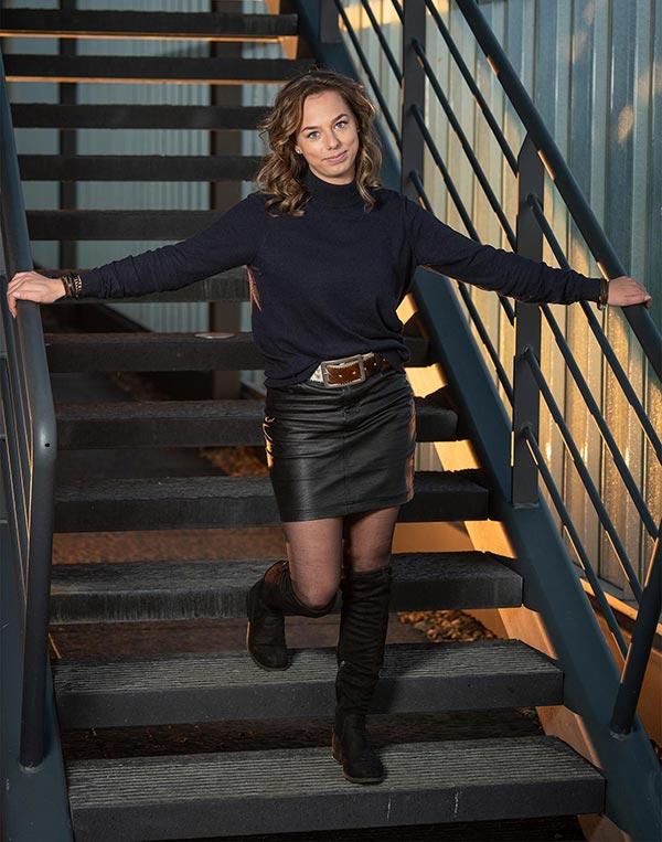 Sfeerfoto schoonheidsspecialiste & nagelstyliste Danjel Holterman staand op een retro trap.