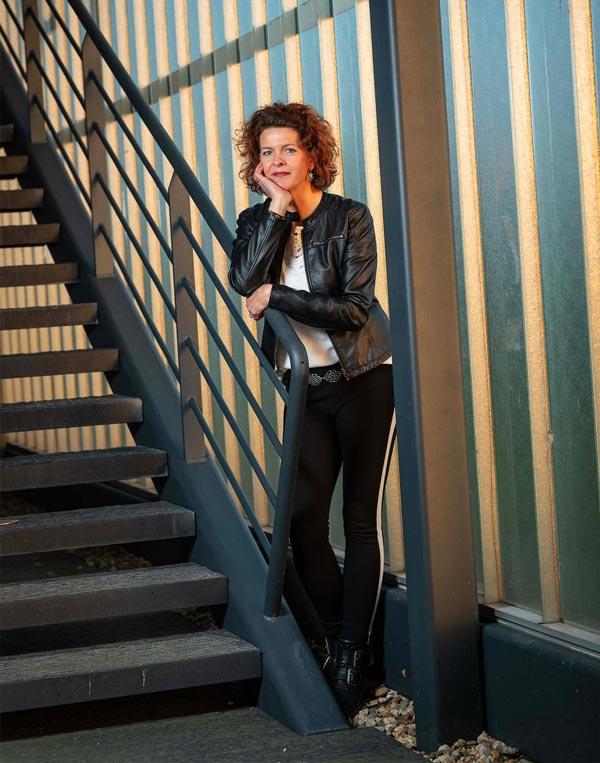 Sfeerfoto haarstyliste Dorien Mink leunend op de leuning retro trap.