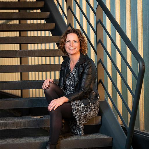 Sfeerfoto haarstyliste en krullenspecialiste Kristel Schutten zittend op een retro trap.