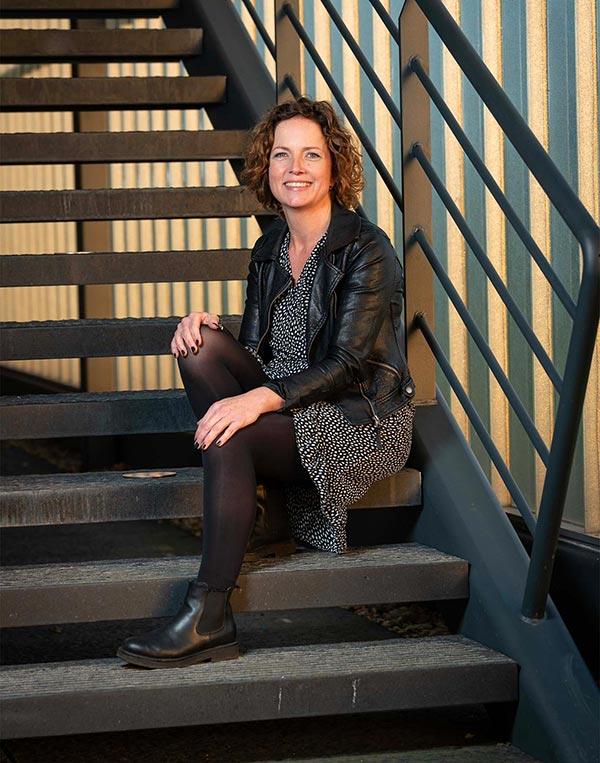 Sfeerfoto haarstyliste en krullenspecialist Kristel Schutten zittend op een retro trap.