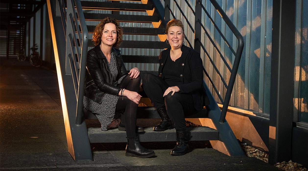 Sfeerfoto eigenaressen Perron 84: Kristel Schutten en Sabrina Nijhof zitten op een trap in retro stijl.