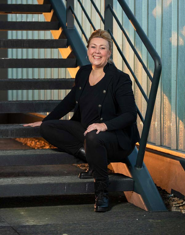 Sfeerfoto Sabrina Nijhof: visagiste, kapster in Enter en hoofdhuidspecialiste zittend op een retro trap.
